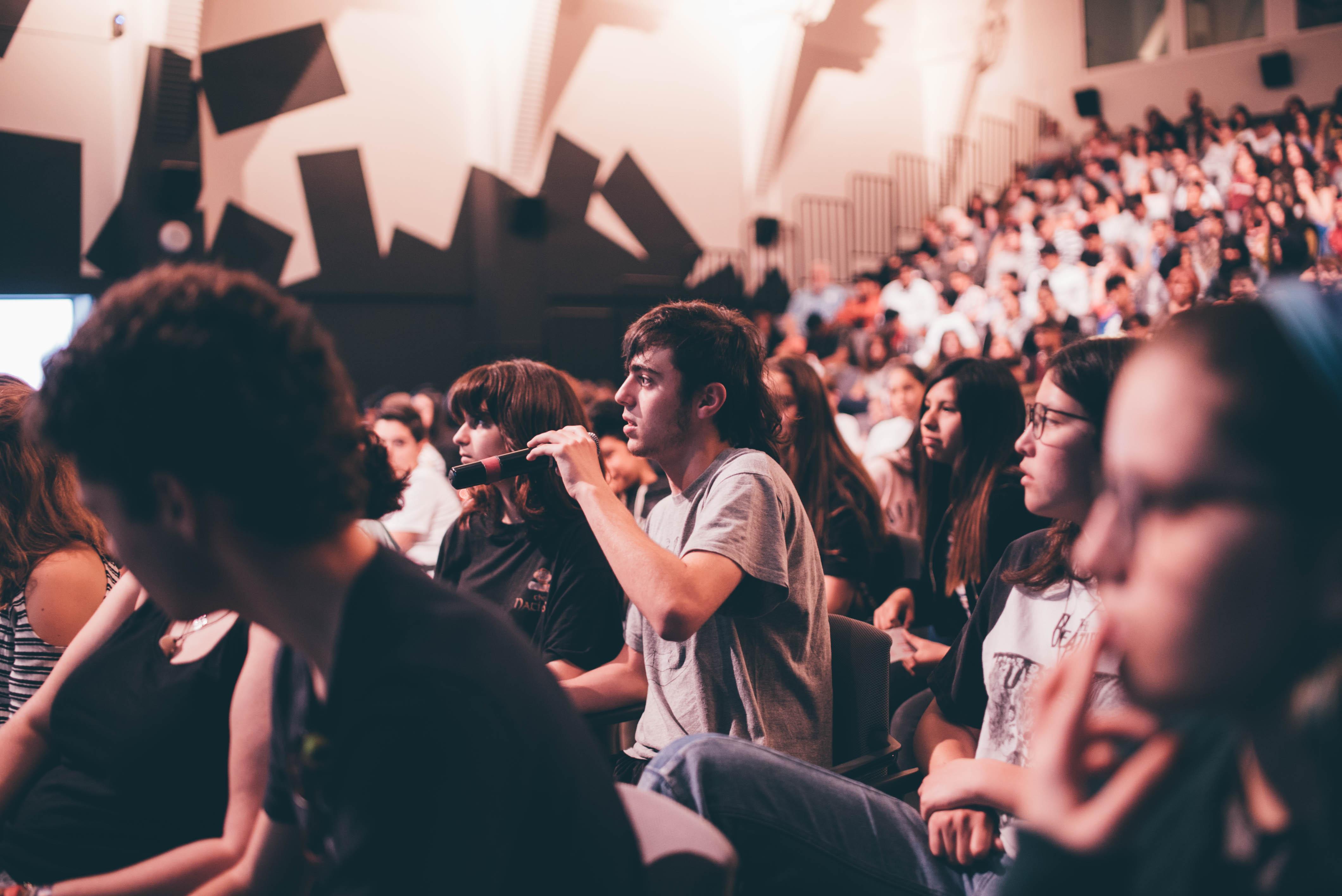 Público adolescente haciendo preguntas en un coloquio de cine.